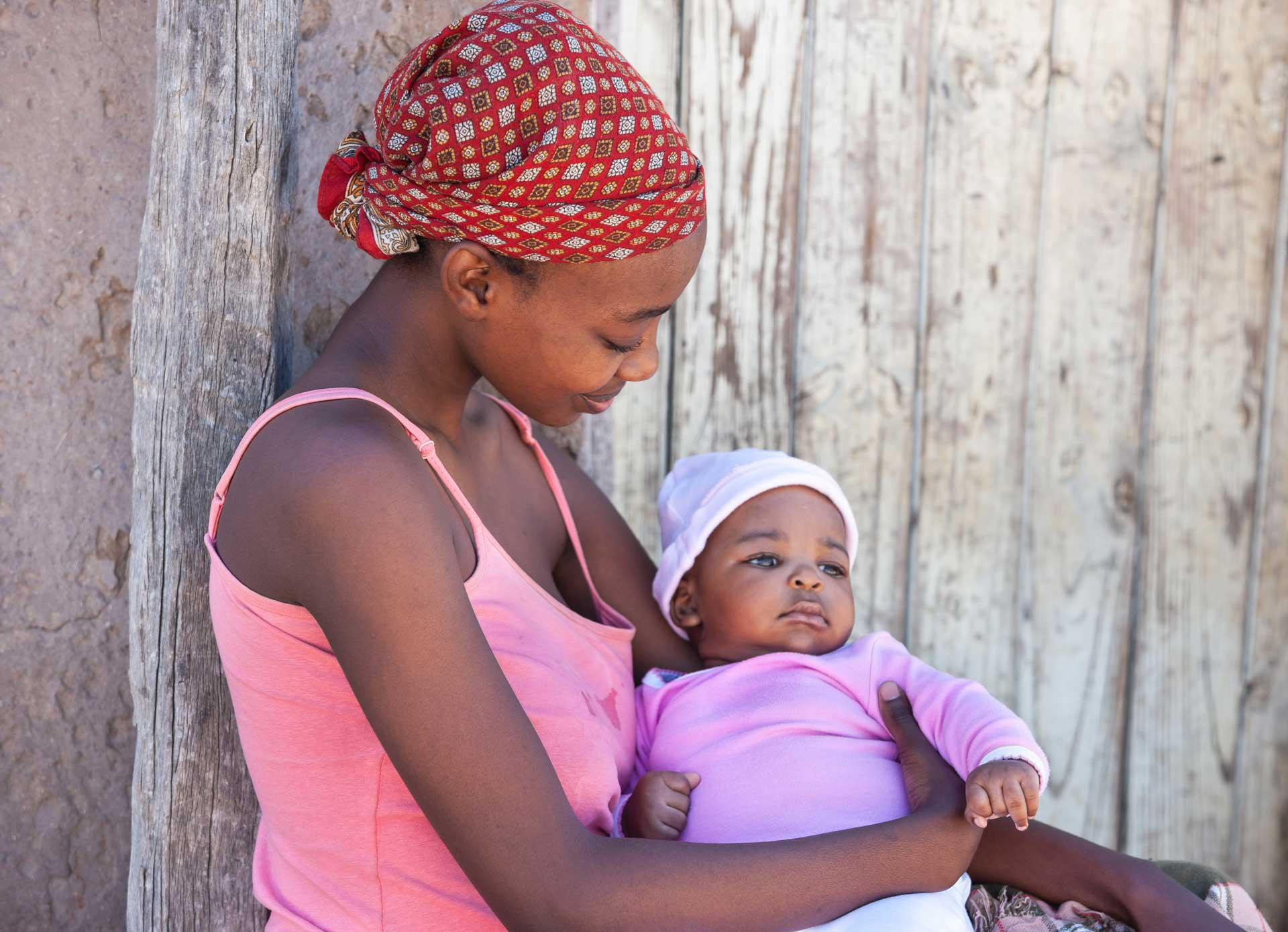 African woman holding baby while looking at him lovingly.